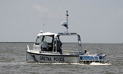 06 June 2010. Barataria Bay to Grand Isle, Jefferson/Lafourche Parish, Louisiana. <br /> A police boat patrols Barataria Bay which has been closed to all fishermen, commercial and recreational for the past two weeks. The ecological and economic impact of BP's oil spill is devastating to the region. Oil from the Deepwater Horizon catastrophe is evading booms laid out to stop it thanks in part to the dispersants which means the oil travels at every depth of the Gulf and washes ashore wherever the current carries it. The Louisiana wetlands produce over 30% of America's seafood and are the most fertile of their kind in the world.<br /> Photo; Charlie Varley/varleypix.com