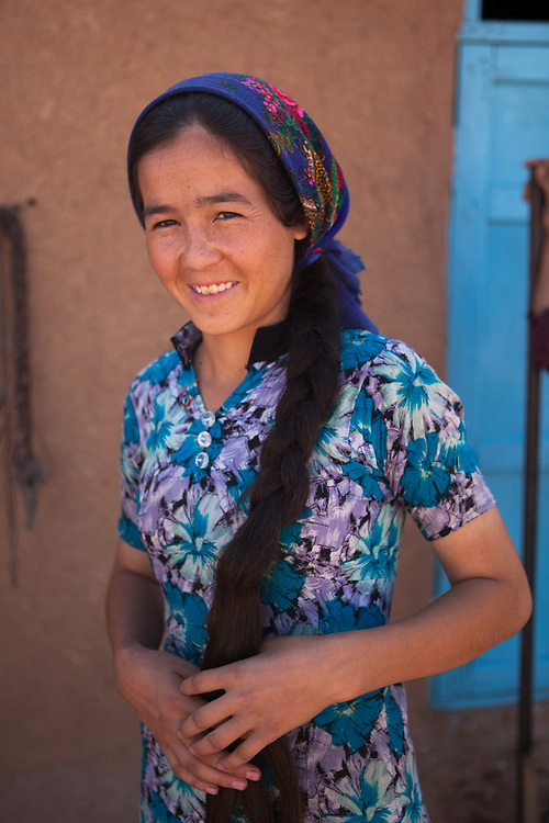 A young woman, with long thick hair, stands outside the family home in the desert village of Damla, Turkmenistan