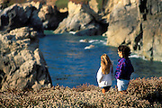 Mother and daughter watching the surf from a cliff along US Highway 1 on the Pacific coast, Big Sur, California