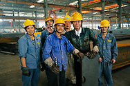 Hangzhou, Zhejiang Province, China. Steelworkers in fabrication shed of the giant Triumpher steel construction works
