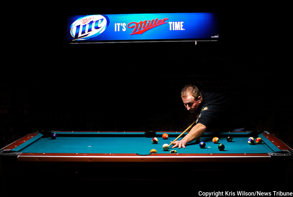 Kris Wilson/News Tribune<br /> Scott Casada lines up to drop the one ball in the side pocket as he, Adam Casada and Morgan McCue get in a few games of pool while watching Monday Night Football at Spectators Sports Bar &amp; Billiards in downtown Jefferson City.