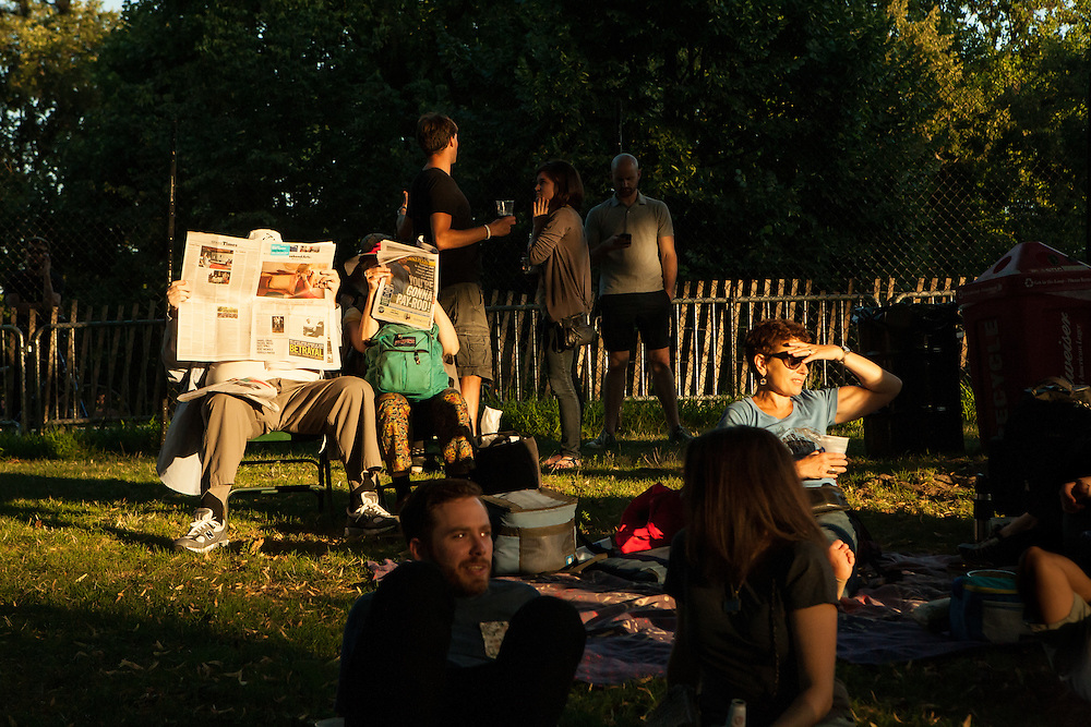 Concert-goers relax on the lawn at sunset in Prospect Park during the first intermission.