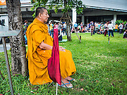 05 AUGUST 2016 - BANGKOK, THAILAND:  A Buddhist monk sits on the front lawn of the Thai Supreme Court building after Yingluck Shinawatra appeared in the Supreme Court of Thailand Friday to start her defense. Yingluck was deposed by a military coup in 2014 and is being tried on corruption and mismanagement charges related to a price support plan for Thai rice farmers that was instituted while she was Prime Minister. More than two years after her government was deposed by a military coup, she is still a popular figure and hundreds of her supporters packed the area around the courthouse to greet her when she arrived at the Court.     PHOTO BY JACK KURTZ