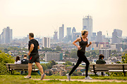 UNITED KINGDOM, London: 22 May 2019 <br /> Joggers run past the London skyline as they make their way over Parliament Hill in Hampstead Heath today. The warm weather is set to continue reaching up to temperatures of 22 C in the capital tomorrow.<br /> Rick Findler / Story Picture Agency