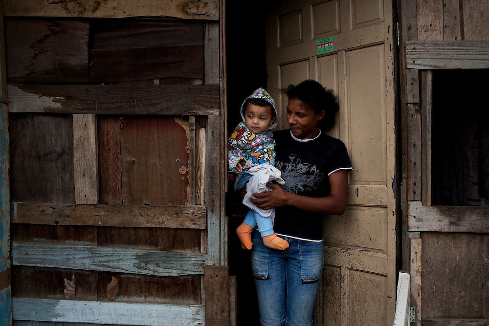 Carla with her baby outsides their home in a favela in Sao Paulo. Carla's son has pneumonia, the doctor has said it is due to the bad living conditions. He is constantly sick, and it worries Carla, since her baby niece died a few months before. They live in a shack built into the side of the hill above the favela (slum), and heavy rain has already once made part of the house collapse on top of her baby who luckily was protected by his cot. Guarulhos, Brazil.
