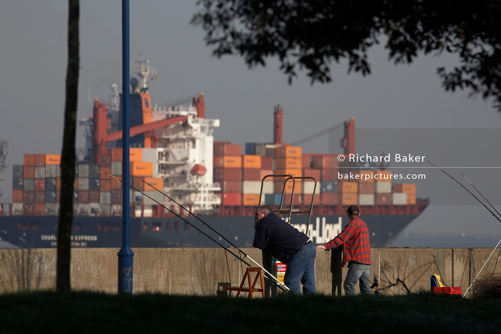 A  Hapag-Lloyd container cargo ship navigates past two fishermen on the southern shores of the River Thames at Gravesend, Kent England. Pausing from their fishing, the two men lean over the sea defence wall to watch the traffic to-and-fro as one giant vessel after another departs from Tilbury Docks towards open sea. The Thames has historically long been a route for shipping that kept the capital supplied and although the docks have seen huge decreases in traffic and volume since the second world war, Tilbury remains a busy hub for containerized vessels arrivng from all over the world. There are 133 Hapag-Lloyd containerships with a capacity of around 499.000 TEU (Twenty foot containers), Container capacity exceeds 1,1 million (TEU) containers.