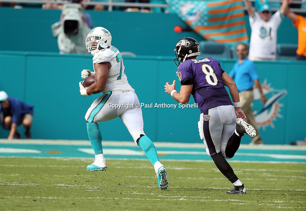 Miami Dolphins defensive end Derrick Shelby (79) laughs while looking back at Baltimore Ravens quarterback Matt Schaub (8) as he returns a tipped pass for an 11 yard second quarter touchdown and a 15-0 Dolphins lead during the 2015 week 13 regular season NFL football game against the Baltimore Ravens on Sunday, Dec. 6, 2015 in Miami Gardens, Fla. The Dolphins won the game 15-13. (©Paul Anthony Spinelli)