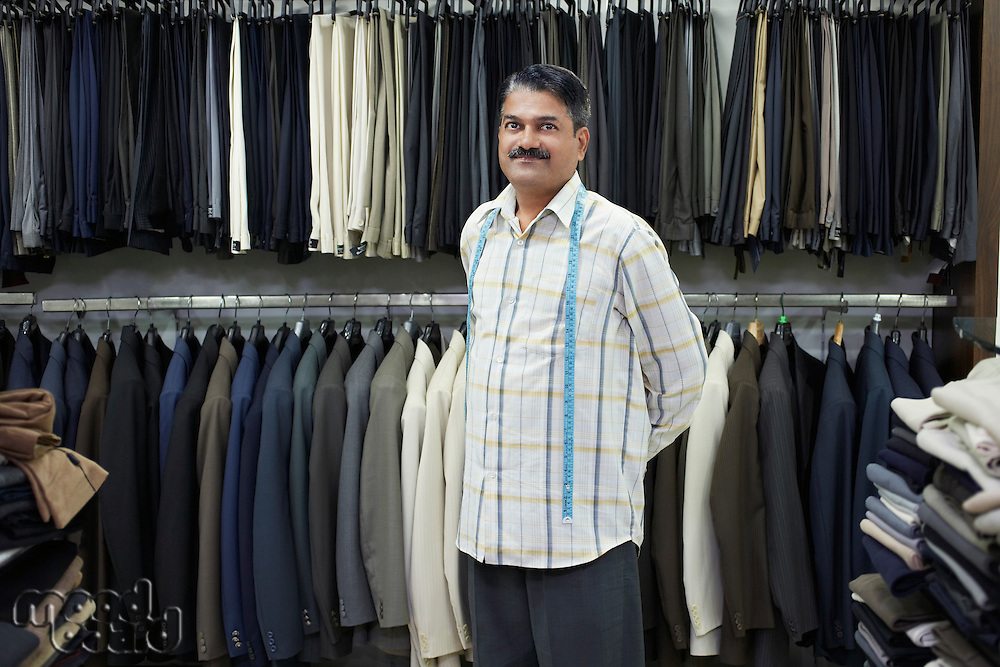 Tailor standing in shop in front of clothes racks portrait