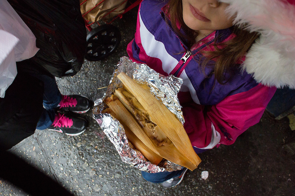 A girl eats a tamale near the 82nd Street subway station, where three Mexican women regularly vend tamales and hot drinks from shopping carts.