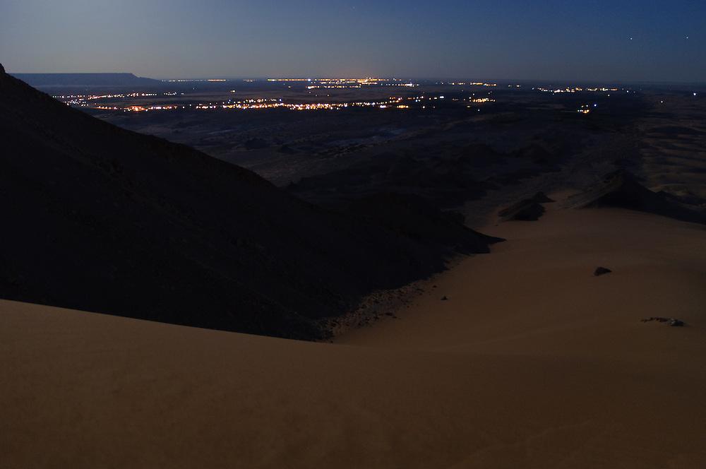 The desert plateau around Al-Qasr, Dakhla Oasis, under a full moon - the lights of Al-Qasr and Mut in the distance