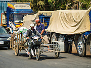 "15 FEBRUARY 2016 - ARANYAPRATHET, SA KAEO, THAILAND:  A motorcycle owner in Aranyaprathet, Thailand, pulls a load of bottled water to the Cambodian side of the border. Thais selling bottled water in the border town of Aranyaprathet, opposite Poipet, Cambodia, have reported a surge in sales recently. Cambodian officials told their Thai counterparts that because of the 2016 drought, which is affecting Thailand and Cambodia, there have been spot shortages of drinking water near the Thai-Cambodian and that ""water shortages in Cambodia had prompted people to hoard drinking water from Thailand.""    PHOTO BY JACK KURTZ"