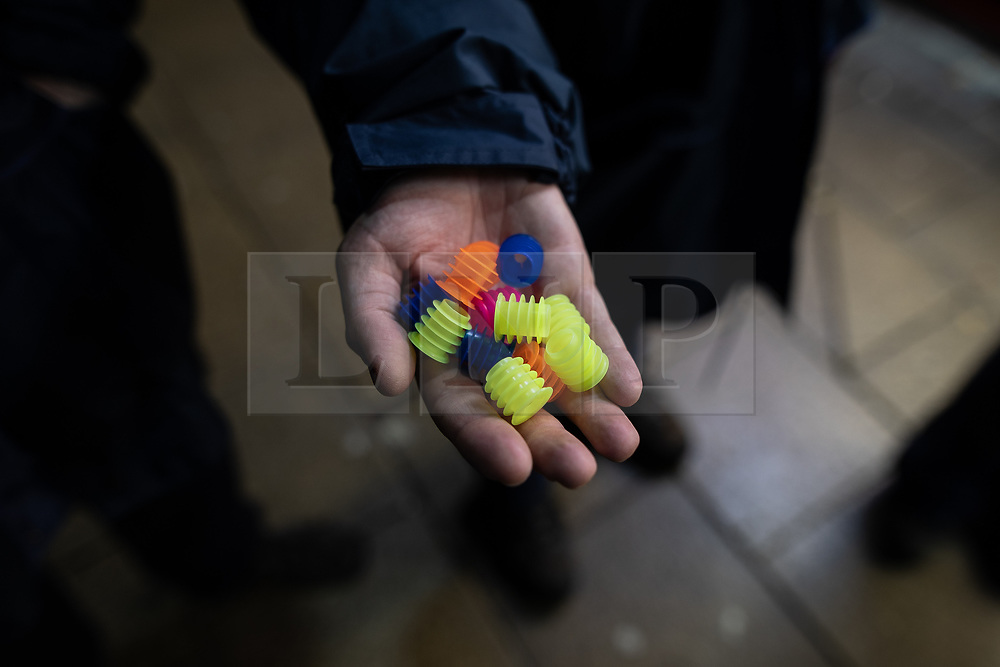 """© Licensed to London News Pictures . 27/12/2018. Wigan, UK. A street pastor holds out a handful of """" Spikeys """" - devices designed to prevent drinks from being spiked . Revellers in Wigan enjoy Boxing Day drinks and clubbing in Wigan Wallgate . In recent years a tradition has been established in which people go out wearing fancy-dress costumes on Boxing Day night . Photo credit: Joel Goodman/LNP"""
