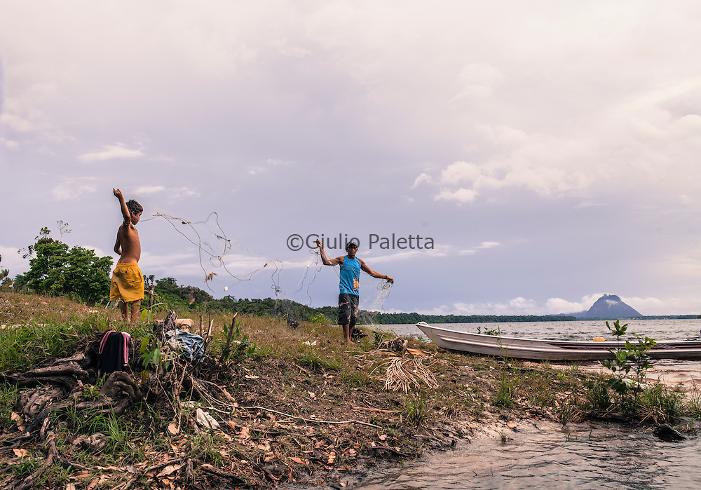 """Grandfather and his grandson fizing a fishing net in a community near Cucui, on the Brazilian side of the triple border between Brazil, Colombia and Venezuela in the Amazon. On the background,  the """"Pedra do Cucui"""" a spectacular rocky formation in the Venezuelan territory"""