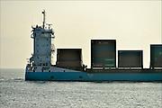 Nederland, Vlissingen, 14-9-2014 Een kustvaarder met containers vaart bij Vlissingen vanaf de Westerschelde naar de Noordzee. Vanaf het strand van Walcheren bij Dishoek heb je mooi zicht op de scheepsbewegingen. Het is een kustvaarder. FOTO: FLIP FRANSSEN/ HOLLANDSE HOOGTE