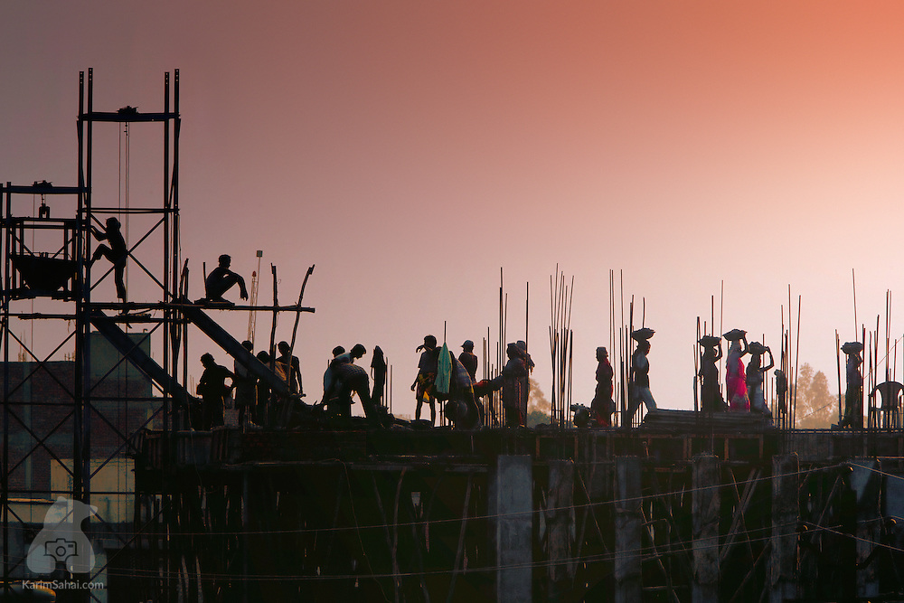 Construction workers on top of a building appear as silhouettes against the dusky sky. While the social system of castes (jati) has seen many reform attempts, the stratification of society according to occupation is still very much a fact of life in India.