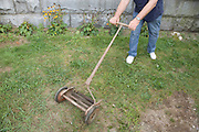 male person cutting grass with an old lawnmower