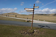 Walkers pass-by on a windy day, by a leaning signpost pointing to Malham and Settle, in the Yorkshire Dales National Park on 12th April 2017, in Malham, Yorkshire, England.