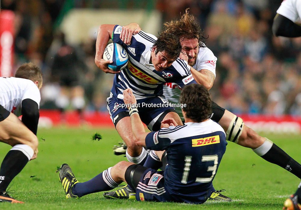 Stormers lock De Kock Steenkamp (C) is tackled by Sharks lock Ross Skeate(C-R) during their Super Rugby match against the Sharks in Cape Town, South Africa 30 April 2011