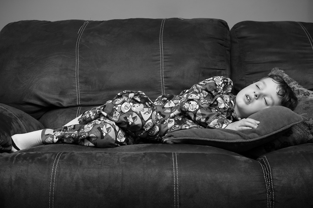 Photo of boy sleeping on the couch in his angry birds pajamas.