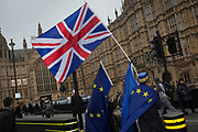 As MPs debate the timing of Brexit inside the House of Commons, pro-Europe/anti-Brexit protesters wave EU and Union Jack flags outside Parlament, on 15th November 2017, in Westminster, London, England.