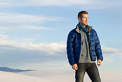 hot man outdoors in a down jacket and scarf at sunset