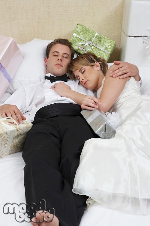 Bride and groom sleeping among presents
