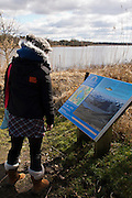 Annandale Way,  Lochmaben. Young woman wearing black jacket, grey wooly hat and beige boots reads information panel looking over the water on a sunny overcast day.