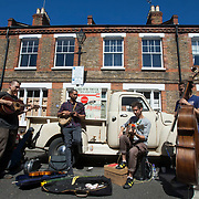 The Debt Collective band busk on Columbia Road during the Sunday flower market. Folk music