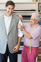 Tailor assisting young customer in custom made suit