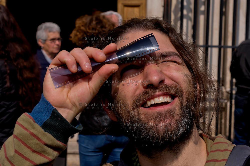 Roma 20 Marzo 2015<br /> Eclissi solare parziale al quartiere San Lorenzo. La gente si riunita questa mattina in Piazza Immacolata, per osservare  l'eclissi solare parziale. Un uomo guarda l' eclissi solare parziale attraverso una pellicola fotografica.<br /> Rome March 20, 2015<br /> Partial solar eclipse. People gather this morning in Piazza Immacolata, District San Lorenzo, to get a rare glimpse of the solar eclipse. A man  looks at a partial solar eclipse through an photographic film.