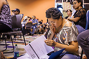 """18 AUGUST 2012 - PHOENIX, AZ:  A young woman goes over the paperwork needed to get into a local community college and qualify for """"deferred action"""" status during a deferred action workshop to start in Phoenix. More than 1000 people attended a series of 90 minute workshops in Phoenix Saturday on the """"deferred action"""" announced by President Obama in June. Under the plan, young people brought to the US without papers, would under certain circumstances, not be subject to deportation. The plan mirrors some aspects the DREAM Act (acronym for Development, Relief, and Education for Alien Minors), that immigration advocates have sought for years. The workshops were sponsored by No DREAM Deferred Coalition.  PHOTO BY JACK KURTZ"""