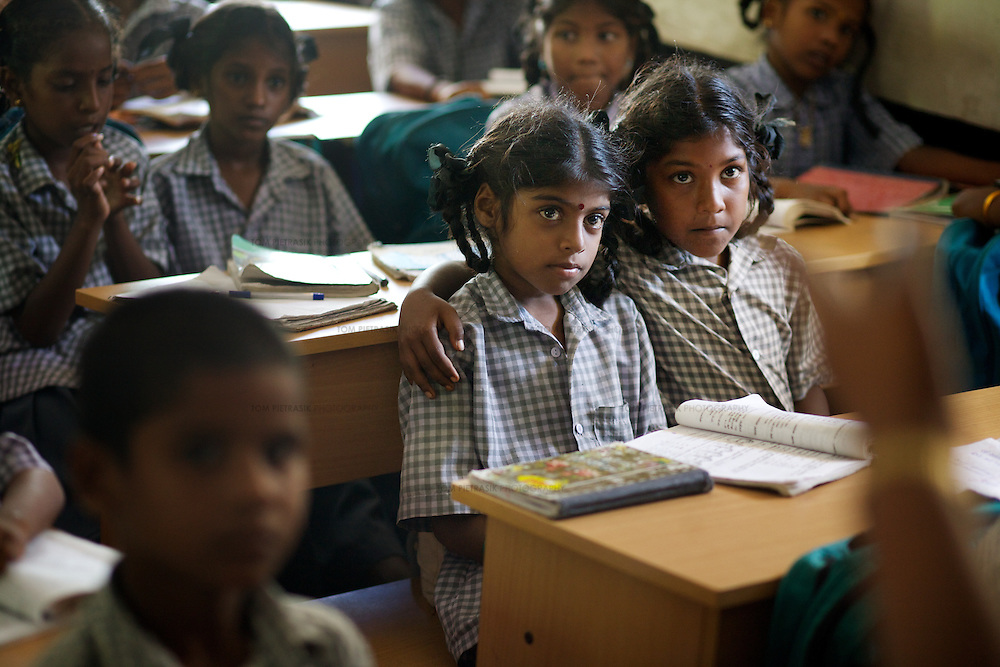 Viyashree Viswanathan (centre with large bindi on forehead) in her 5th Standard class at the Thalanuda Government School. Vijyashree's grades have been falling in recent months. The benches on which Vijyashree and her fellow students work were supplied by Unicef following the tsunami.<br /><br />Vijitha and Vijyashree Viswanathan, now age 12 and 10, lost their mother and younger brother to the 2004 Asian Tsunami. The sisters continue to live with their father Viswanathan in a small house in the fishing village of Thalanguda, 5km from Cuddalore. The house does not have a toilet and water is supplied for only a short period of the day. Viswanathan married Kayalvizhi just over a year after the tsunami and the couple now have a son born in December 2006. Of the two sisters it was the elder Vijitha who initially appeared more distressed at her mother's death. But in the subsequent three years she has come to terms with her loss and seems better equipped to face the challenges of growing up without the support of her mother. In contrast Vijyashree, whos younger age may have insulated her from some of the grief experience by her sister, has fallen back in her studies becoming moody, withdrawn and reticent. Vijyashree has suffered fits for a number of years but in the past twelve months these have become more frequent. Viswanathan blames the drugs prescribed to treat his daughter's condition for her moodiness. Another explanation could be the arrival of Vijyashree's half-brother Sanjay with whom she must now compete for the affections of her father. Kayalvizhi does not appear particularly sensitive to the needs of her adopted daughters though her position cannot be easy, particularly when burdened with the task of raising a baby. Viswanathan's sister-in-law Shanthi is especially scathing of Kayalvizhi's indifference to Vijitha and Vijyashree and questions whether the girls should be expected to clean the house, clean utensils and prepare themselves for school. Shanthi compl