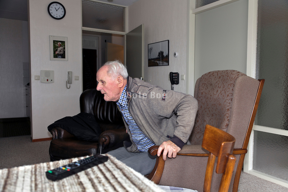 elderly person getting up from armchair
