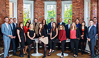Large group shot in featuring sales team take in modern office with bare red brick walls and windows behind