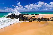 Lava rocks and surf on Secret Beach (Kauapea Beach), Island of Kauai, Hawaii