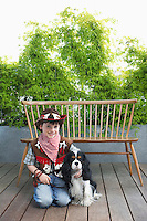 Boy (7-9) wearing cowboy costume kneeling with dog on decking