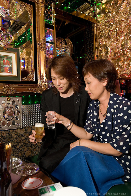"""Yumi (R) drinking with her host Shun (L) in club """"Ai"""". Club """"Ai"""" (love in Japanese) is one of the oldest host clubs in Kabukicho entertainment area near Shinjuku. It started functioning 37 years ago, with hosts ready to take care of the needs of their female customers. The customers have to pay from 5000 friendly price for beginners, to millions of yen, depending on how good the host is in pleasing the customer and encouraging her to buy drinks. On top of these a good host can receive expensive gifts from his regular customers.  Tokyo - JAPAN"""