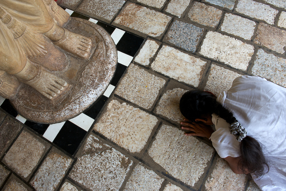A pilgrim prostrates herself in prayer at a standing buddha statue,  Ruwanwelisaya Chedi, Anuradhapura, Sri Lanka