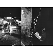 A Salvadoran policeman stands in the shadow of a building rifle at the ready as panicked people scramble after hearing explosions nearby.  San Salvador 1981 Ed Hille