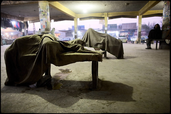 """Homeless people sleep on beches at the main bus station. Islamabad, Pakistan, on friday, November 28 2008.....""""Pakistan is one of the countries hardest hits by the narcotics abuse into the world, during the last years it is facing a dramatic crisis as it regards the heroin consumption. The Unodc (United Nations Office on Drugs and Crime) has reported a conspicuous decline in heroin production in Southeast Asia, while damage to a big expansion in Southwest Asia. Pakistan falls under the Golden Crescent, which is one of the two major illicit opium producing centres in Asia, situated in the mountain area at the borderline between Iran, Afghanistan and Pakistan itself. .During the last 20 years drug trafficking is flourishing in the Country. It is the key transit point for Afghan drugs, including heroin, opium, morphine, and hashish, bound for Western countries, the Arab states of the Persian Gulf and Africa..Hashish and heroin seem to be the preferred drugs prevalence among males in the age bracket of 15-45 years, women comprise only 3%. More then 5% of whole country's population (constituted by around 170 milion individuals),  are regular heroin users, this abuse is conspicuous as more of an urban phenomenon. The substance is usually smoked or the smoke is inhaled, while small number of injection cases have begun to emerge in some few areas..Statistics say, drug addicts have six years of education. Heroin has been identified as the drug predominantly responsible for creating unrest in the society."""""""