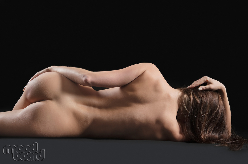 Back view of nude woman lying on side over black background