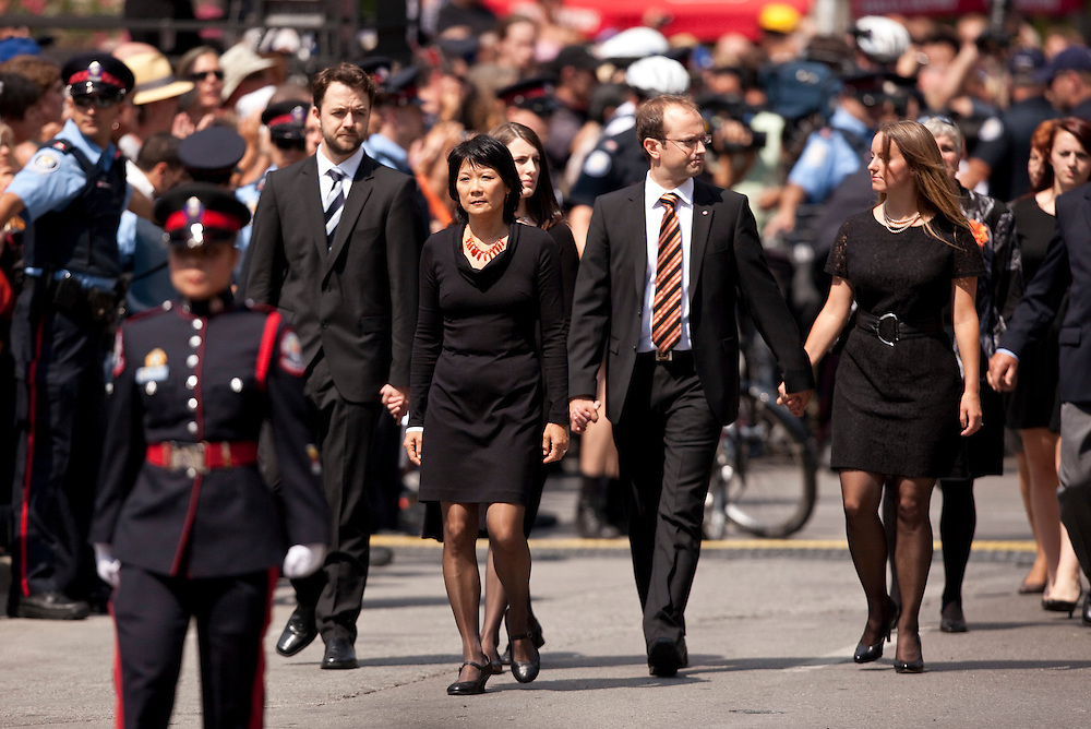 Toronto, Ontario ---11-08-27--- Olivia Chow, wife of Jack Layton, andhis children walk through the streets of Toronto, Ontario during a funeral procession for the late NDP leader August 27, 2011. <br /> AFP/GEOFF ROBINS/STR