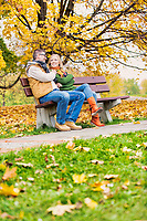 Portrait of attractive man sitting on bench while talking to his beautiful wife in park