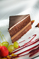 Chocolate cake with strawberry coulis and fresh strawberries and grapes as garnish