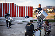 """Father Abdush (right) and his sons Mersid (2nd left), Erdal ( left) and Ergul (on top) during a drum session on a stage in front of the """"House of Culture"""" in Delcevo, Macedonia. The Roma family - father and his 3 sons - are well know for their drum perfomances and also they build their drums themselves."""
