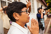 12 APRIL 2013 - BANGKOK, THAILAND:   .A Thai woman prays as the Phra Buddha Sihing is brought out for public viewing on the first day of Songkran. The Phra Buddha Sihing, a revered statue of the Buddha, is carried by truck through the streets of Bangkok so people can make offerings and bathe it in scented oils. Songkran is celebrated in Thailand as the traditional New Year's Day from 13 to 16 April. The date of the festival was originally set by astrological calculation, but it is now fixed. If the days fall on a weekend, the missed days are taken on the weekdays immediately following. Songkran is in the hottest time of the year in Thailand, at the end of the dry season and provides an excuse for people to cool off in friendly water fights that take place throughout the country. The traditional Thai New Year has been a national holiday since 1940, when Thailand moved the first day of the year to January 1. The first day of the holiday period is generally the most devout and many people go to temples to make merit and offer prayers for the new year.  PHOTO BY JACK KURTZ