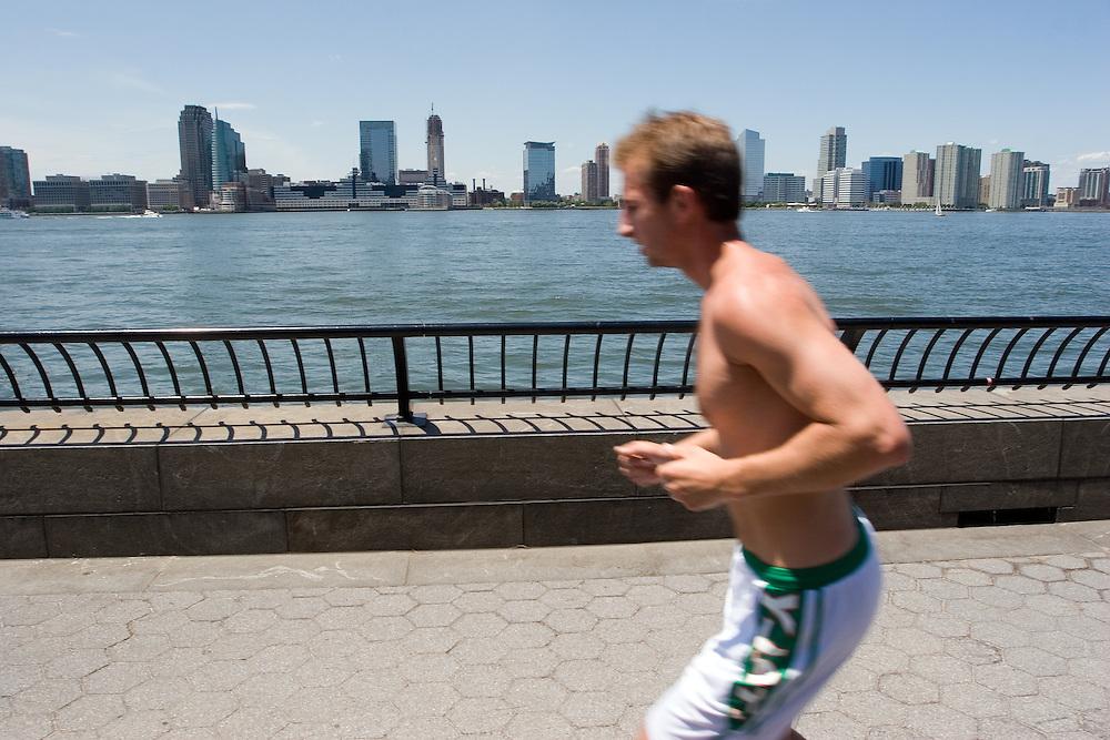 A Newyorker jogging by Hudson River close to Governor Nelson Rockefeller Park. Jersey City in the background.<br /> Un joven neoyorkino hace deporte junto al el r&iacute;o Hudson cerca del Governor Nelson Rockefeller Park, con los edificios de Jersey City al fondo.