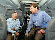 IN FLIGHT - AUGUST 23:  The merged US Airways - America West Vice Chairman Bruce Lakefield (L), and Chairman, President, and Chief Executive Officer Doug Parker (R) chat during a flight to Pittsburgh after a news conference unveiling America West - US Airways new branding, August 23, 2005 in Philadelphia, Pennsylvania. The new airplane paint scheme will represent the combined airlines when the merger takes place. The airline also incorporated Heritage marks upon the airplanes that incorporate classic logos of some of the largest airlines that have merged over the years to create the new US Airways: Allegheny Airlines, America West, Pacific Southwest Airlines, and Piedmont Airlines. (Photo by William Thomas Cain/Getty Images)