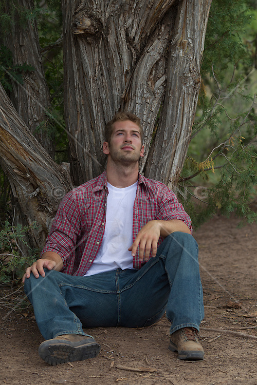 All American man thinking while sitting under a tree