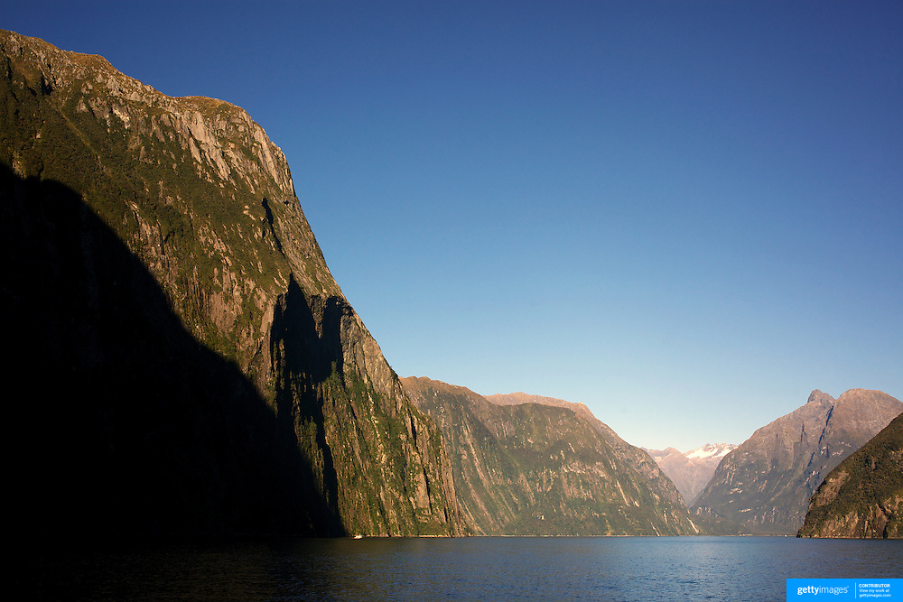 Milford Sound (Piopiotahi in M?ori) is a fjord in the south west of New Zealand's South Island, within Fiordland National Park and the Te Wahipounamu World Heritage site. It has been judged the world's top travel destination and is acclaimed as New Zealand's most famous tourist destination..Milford Sound runs 15 kilometres inland from the Tasman Sea at Dale Point - the mouth of the fiord - and is surrounded by sheer rock faces that rise 1,200metres (3,900ft) or more on either side. Among the peaks are The Elephant at 1,517metres (4,977ft), said to resemble an elephant's head and The Lion, 1,302metres (4,272ft), in the shape of a crouching lion. Lush rain forests cling precariously to these cliffs, while seals, penguins, and dolphins frequent the waters and whales can be seen sometimes..Milford Sound sports two permanent waterfalls all year round, Lady Bowen Falls and Stirling Falls. After heavy rain many hundreds of temporary waterfalls can be seen running down the steep sided rock faces. .The beauty of this landscape draws thousands of visitors each day, with between 550,000 and 1 million visitors in total per year. This makes the sound one of New Zealand's most-visited tourist spots, and also the most famous New Zealand tourist destination.  Milford Sound, New Zealand. 29th April 2011. Photo Tim Clayton